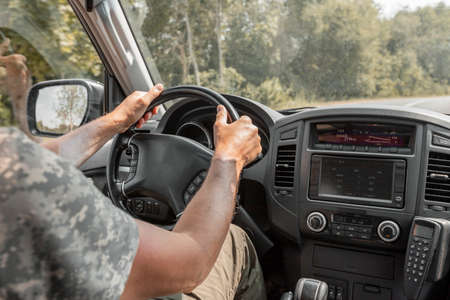 Closeup of men hands holding steering wheel and driving in nature. Road trip of man inside auto during summer holiday travel. Stock Photo