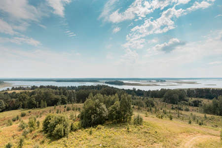 Summer nature landscape with sky, clouds, grass, forest trees and water lakes in the bottom. Rural scenery. Natural scene.
