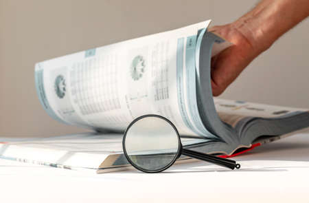 Technical book with turning pages, male hand and magnifier. Engineer research.