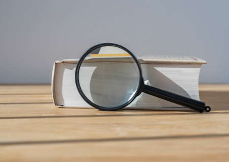 Magnifying glass with close thick book on wood table with day light. Stock Photo