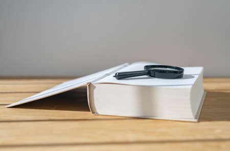 Magnifier with open thick book on wooden desk with daylight.