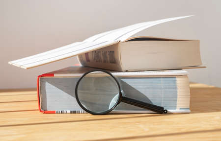 Magnifier near stack of close and open thick books on wooden desk with daylight.