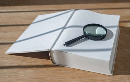 Magnifying lens with open thick book on wood desk with day light. Start from scratch concept.