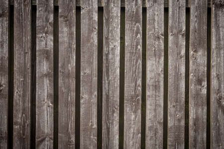 Old shabby natural grey wooden fence background with copy space for text.