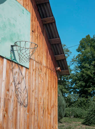 Basketball hoop in nature in summer. Wood wall of house with net for playing. Stock Photo