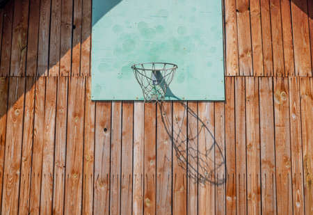 Basketball hoop on wood wall of house with net for playing, sun light and shadow. Stock Photo