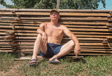 Portrait of man with wooden timbers, logs and planks in summer. Handyman resting in nature outdoors.