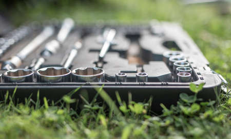 Metal steel repair tools in box on green grass closeup. Stock Photo