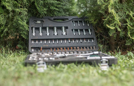 Metal steel repair tools in toolbox on grass outdoors. Stock Photo