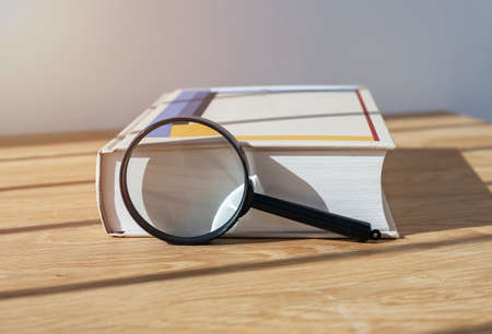Magnifying lens with close thick book for study and reading. Stock Photo