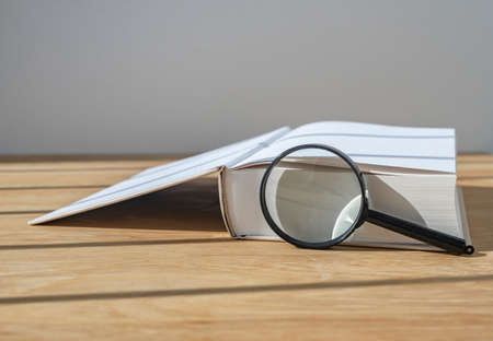 Magnifying lens with open thick book on wood desk with day light.