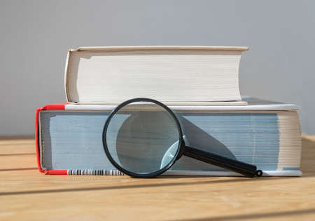 Magnifying glass with stack of close thick books on wooden table with day light.