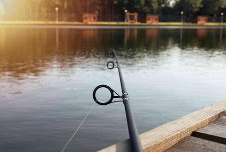 Fishing rod laying on wooden coast over river or lake in summer. Stock Photo