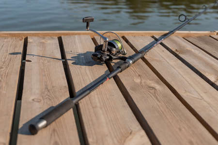 Fishing rod or angler lying on wood coast over river or lake in summer close up.