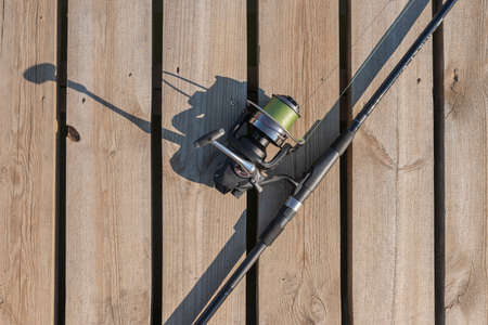 Fishing rod or angler lying on wood surface, top view.