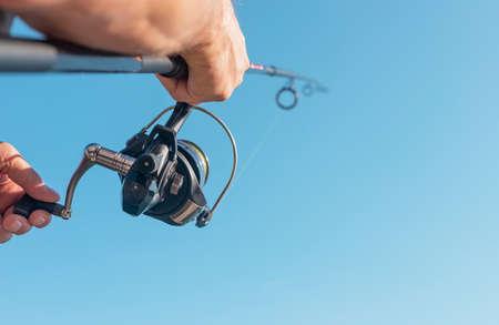 Men hands holding flying fishing rod or angler over blue clear sky.