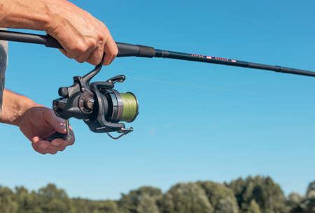 Male hands holding fishing rod or angler over blue clear sky in summer. Stock Photo