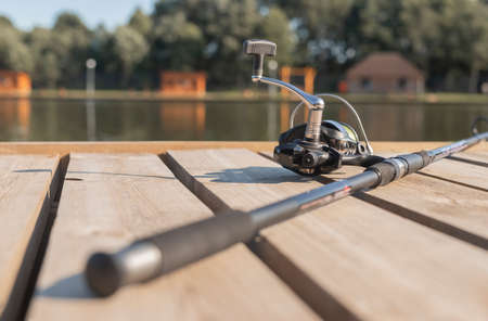 Fishing rod or angler on wood coast over river or lake in summer closeup.