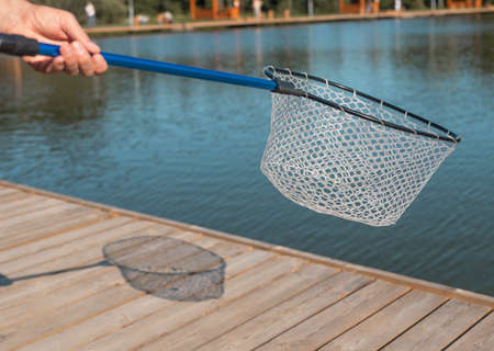 Fishing net of fishnet in male hands over water in summer with sunlight and shadow.