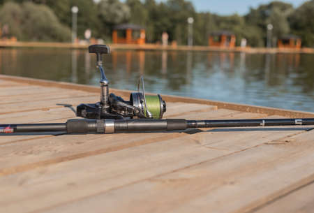 Fishing rod or angler closeup on wood coast over river or lake in summer. Stock Photo