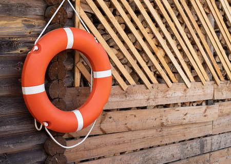 Orange lifebuoy hanging on rope on wooden wall.