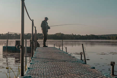 Fisher fishing in foggy morning. Man with fish rod resting on lake in mist. Stock Photo