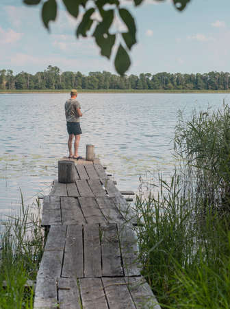 Fisherman back on old wood pier over lake water in summer.