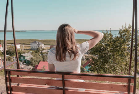 Woman looking into the distance, watching far away, seeing nature, sky, sea, rural landscape. Stock Photo