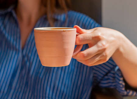 Female hand holding coffee cup closeup.