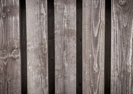 Old natural gray wood fence background with vertical planks.