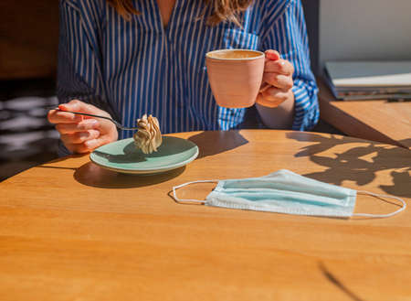 Women hand and coffee cup and sweet dessert and medical face mask on wood desk in coffee house, closeup. Stock Photo