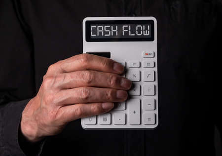 Hand holding calculator with Cah Flow words as concept of black illegal false cashflow. Stock Photo