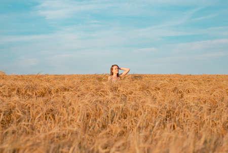 Young woman inside golden wheat field in summer, enjoying nature. Stock Photo