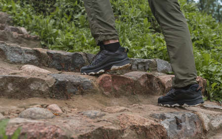 Men legs feet in sneakers climbing up the stairs in nature outdoors. Stock Photo