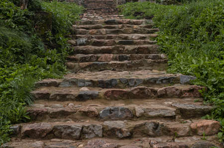 Old ancient stone stairs in nature. Steps among green grass, plants outdoors. Way and path up to temple. Stock Photo
