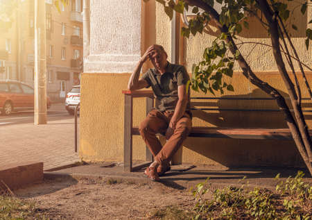 Man with heat stroke sitting on bench, tired of hot temperature, summer weather in city. Stock Photo