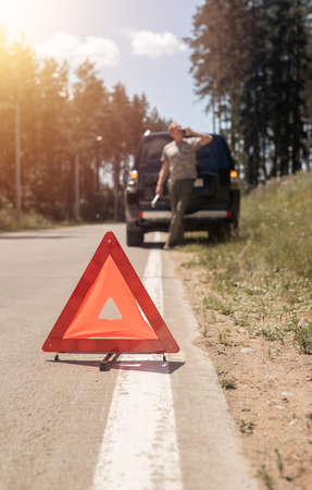 Triangle caution sign on road after car accident and man driver talking on phone, leaning on auto and calling emergency repair service. Stock Photo