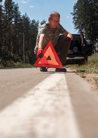 Man driver putting and setting red triangle caution warning sign on road side near broken auto. Stock Photo