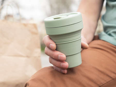 Collapsible silicon eco cup for takeaway coffee. Male hand with sustainable mug. Stock Photo