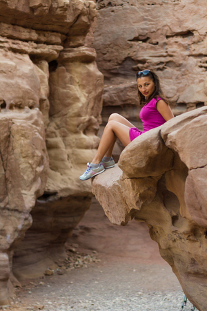 beautiful girl sitting on a rock in Red Canyon Stock Photo