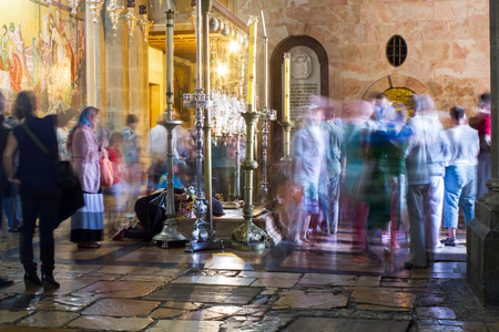 passionately: Jerusalem , Israel - November 02 . 2014 : The pilgrims passionately prays under icon lamps in the church of the Holy Sepulcher . This oldest Christian sanctuary - Stone of Unction