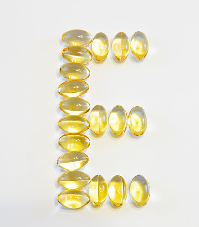 Vitamin E supplement capsules closeup on a white background 写真素材