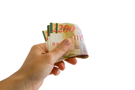 A female hand holding two hundred shekel bank notes against white background. Concept photo of money, banking ,currency and foreign exchange rates.