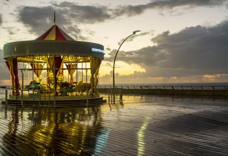Illuminated retro carousel on the seafront at sunset in the rain. Israel Stock Photo