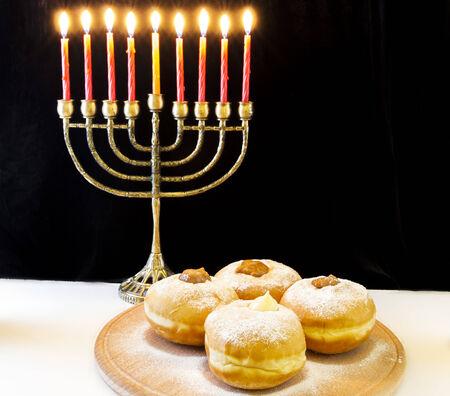 image of jewish holiday Hanukkah with menorah and doughnuts photo