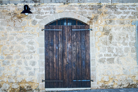 Old rustic wooden gate on stone wall. Stock Photo