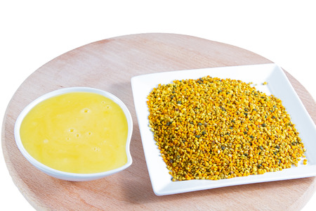 ambrosia: Natural honey and bee pollen isolated on on wooden base .