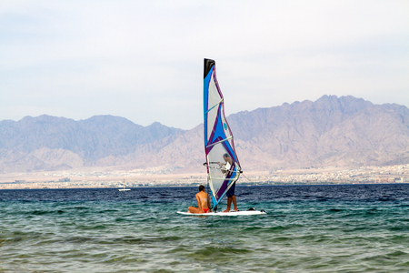 sail board: Eylat , Israel - June 6, 2015: Surfer on a board with a sail . On the Red Sea in the Gulf of Eylat . In the background, the Jordanian mountains.