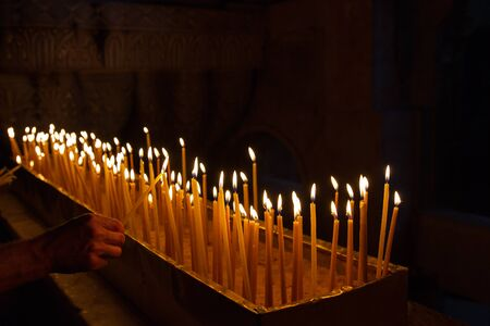 burning: Rows of burning candles in a dim church .