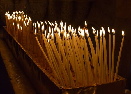 cultic: Rows of burning candles in a dim church .